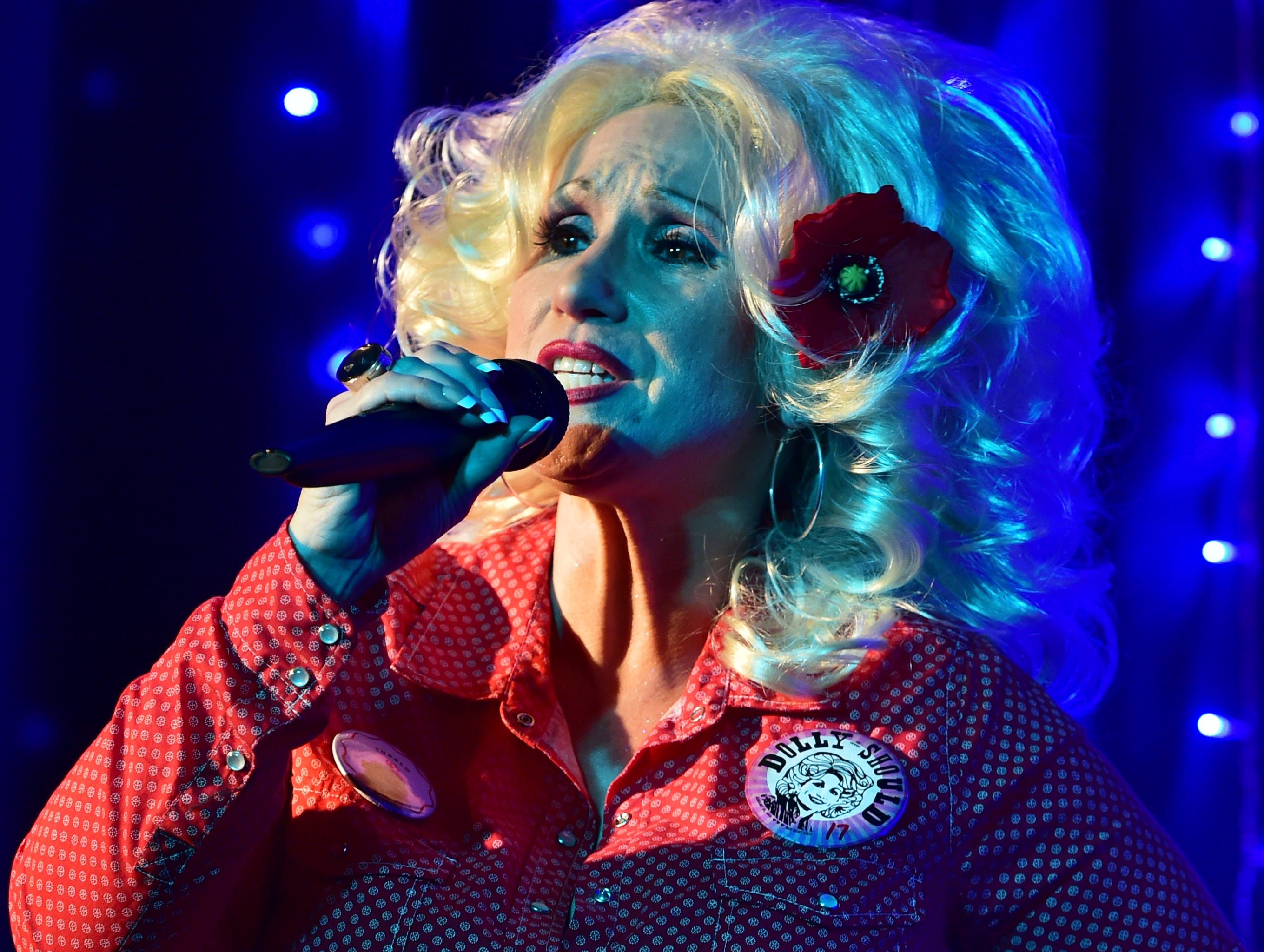 Dolly Parton look-a-like contest winner Cindy Verret sings a karaoke version of a Parton song at 100 Men Hall during the closing celebration of the 4th annual Dolly Should event in Bay St. Louis, Miss. Saturday, Jan. 12, 2019