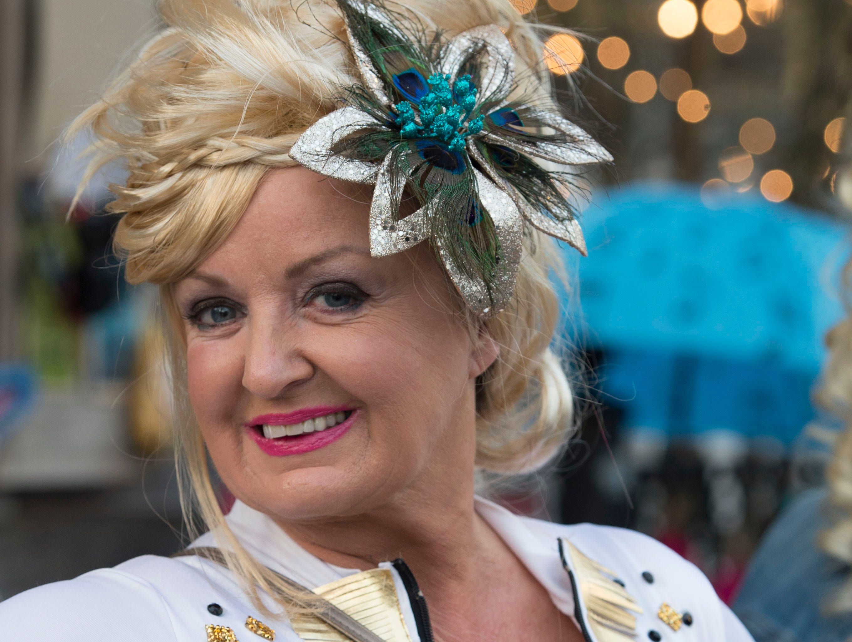An attendee of the 4th annual Dolly Should festival poses before the Dolly Parton look-a-like contest held on the porch of the Mockingbird Cafe. Saturday, Jan. 12, 2019.