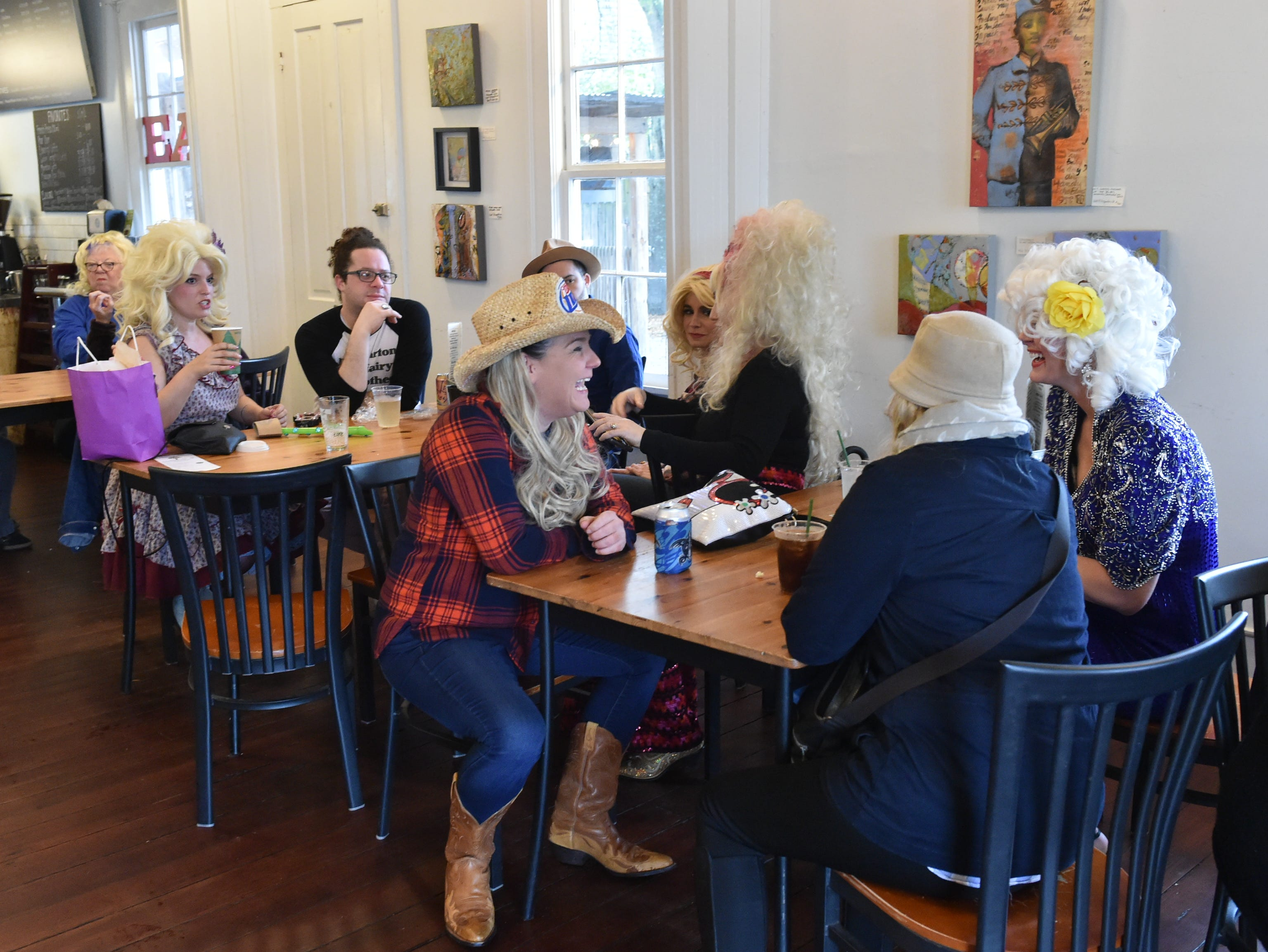 Patrons of the Mockingbird Cafe in Bay St. Louis await the start of the 4th annual Dolly Should festival look-a-like contest held on the steps of the restaurant. Saturday, Jan. 12, 2019.