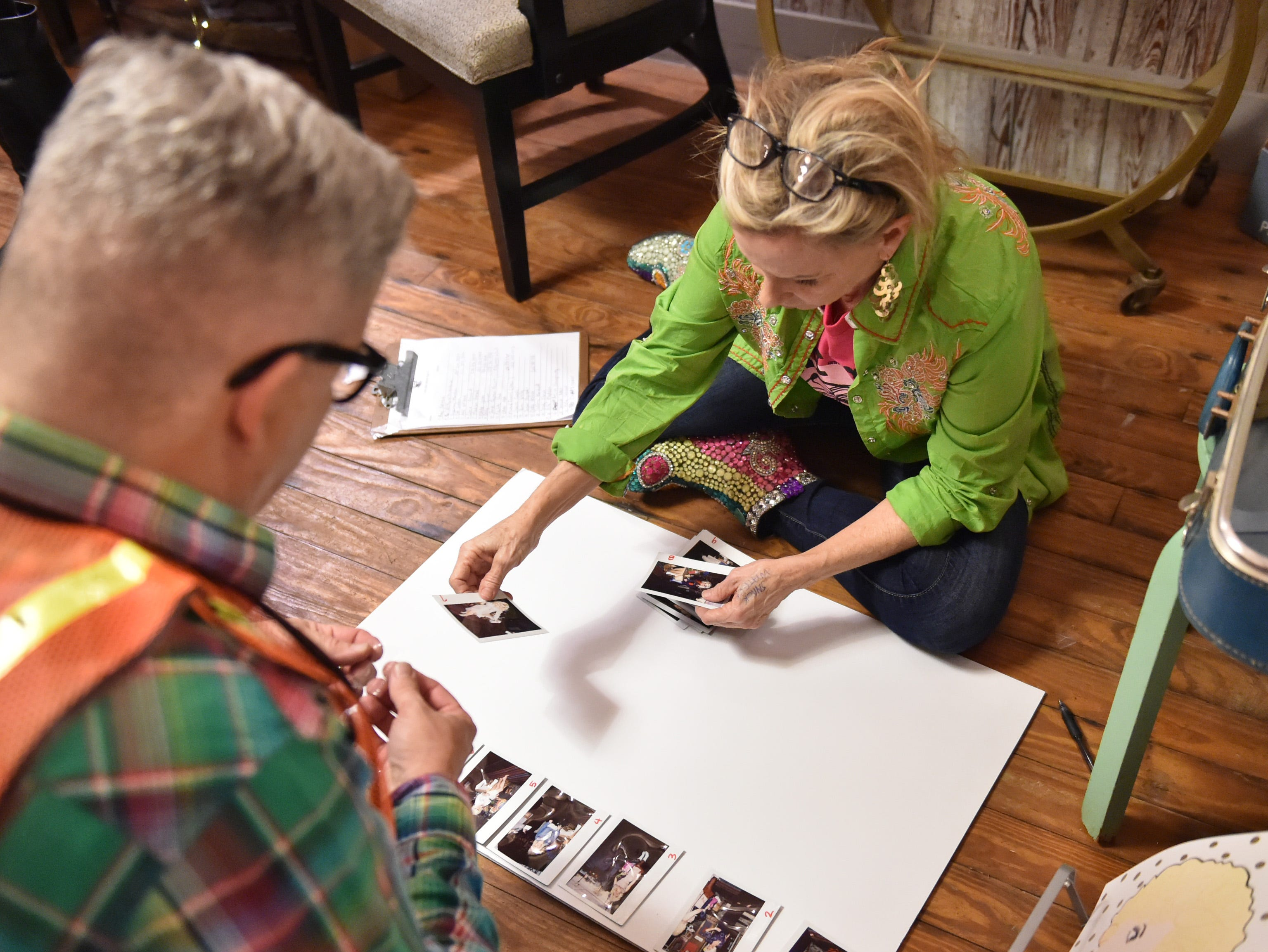 Bay St. Louis silversmith & jewelry artisan Sandy Maggio lays out polaroids of contestants entered in the 4th annual Dolly Should look-a-like contest held on the porch of Mockingbird Cafe. Saturday, Jan. 12, 2019.
