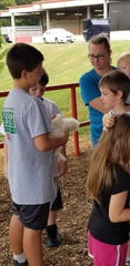 "Ty Atchley loves showing his chickens to other kids. Here he is at ""Down on the Farm Day"" at the Tennessee Valley Fair, where students from kindergarten through third grade enjoy a field trip to get up close and personal with farm animals. Sept. 11, 2018."