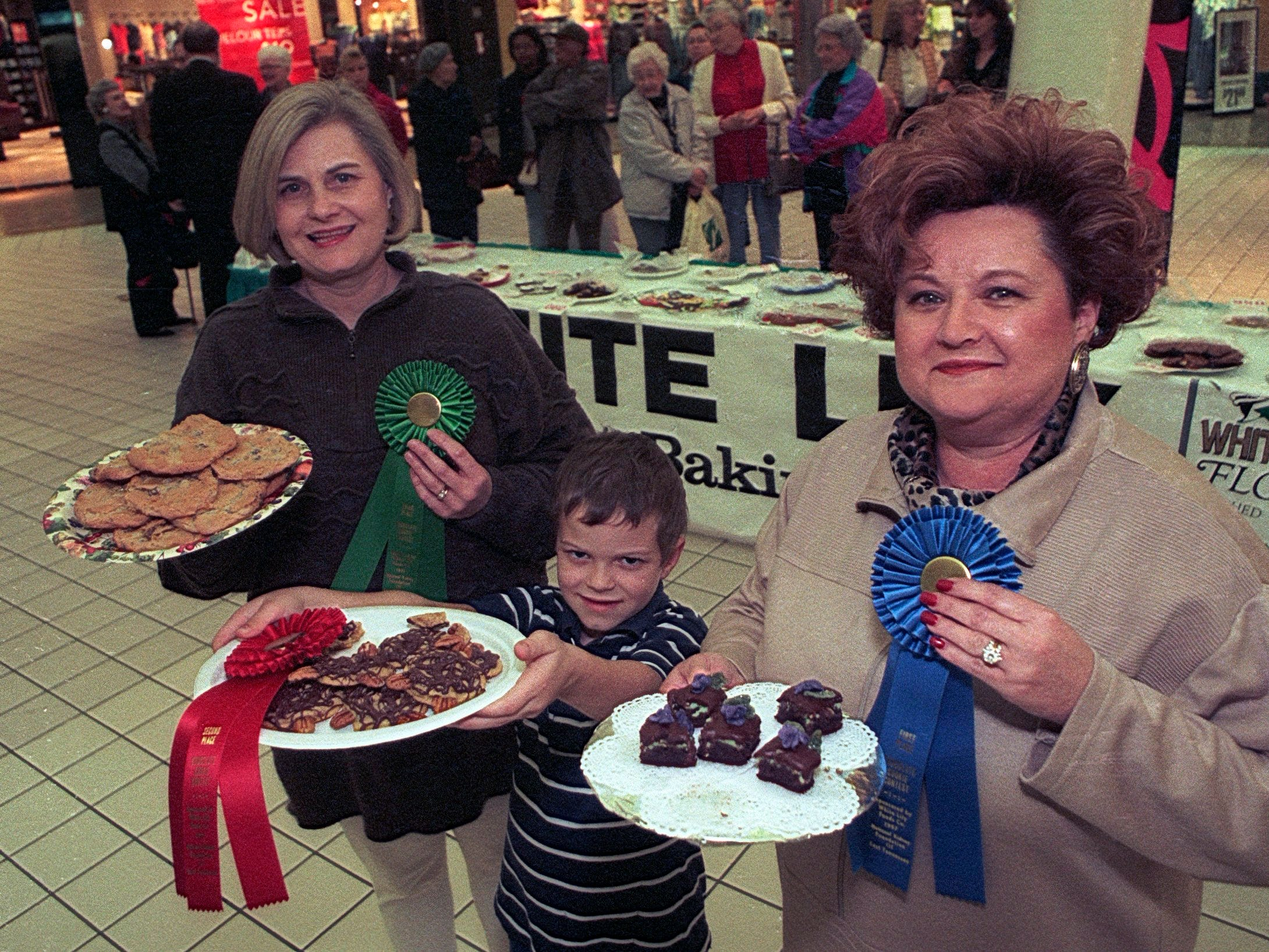Top cookie contest bakers Teresa Lee with chocolate chippers, left, Peter Shankles with chocolately-pecan cartwheels, and Barbara Tenney with gourmet mint brownies show off their winning entries during the Chocolate Fest on Jan. 9, 1997, at East Towne Mall. (News Sentinel Archive)