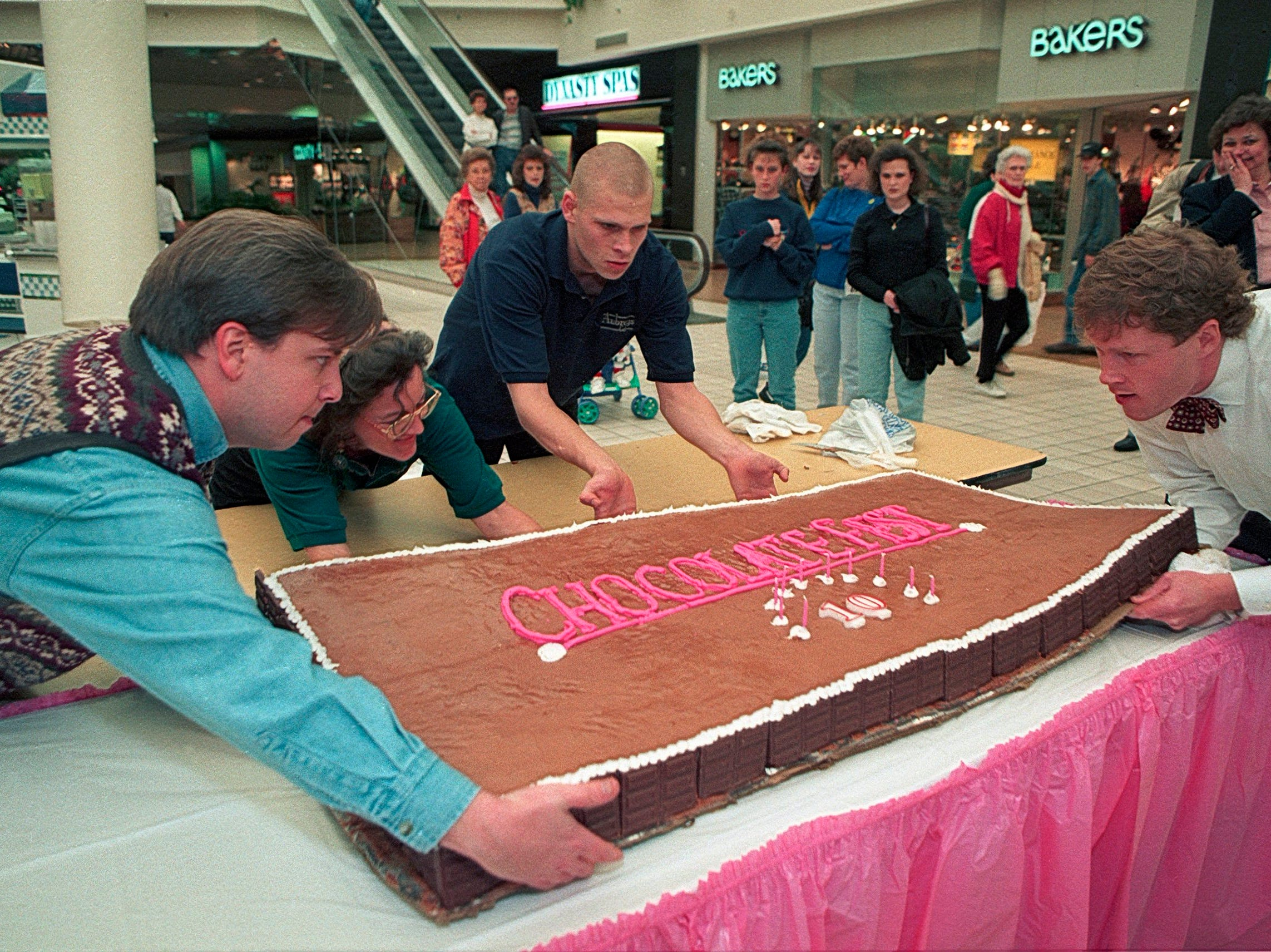 Kurt Ivey, left, Lee Letsinger, Gabe Wilder, and Aubrey's Cafe owner Randy Burleson ready a cake for the tenth anniversary of the Chocolate Fest on Jan. 11, 1996, at East Towne Mall.  Burleson said he used 50 pounds of chocolate candy bars and six two-pound cans of chocolate syrup in the cake.