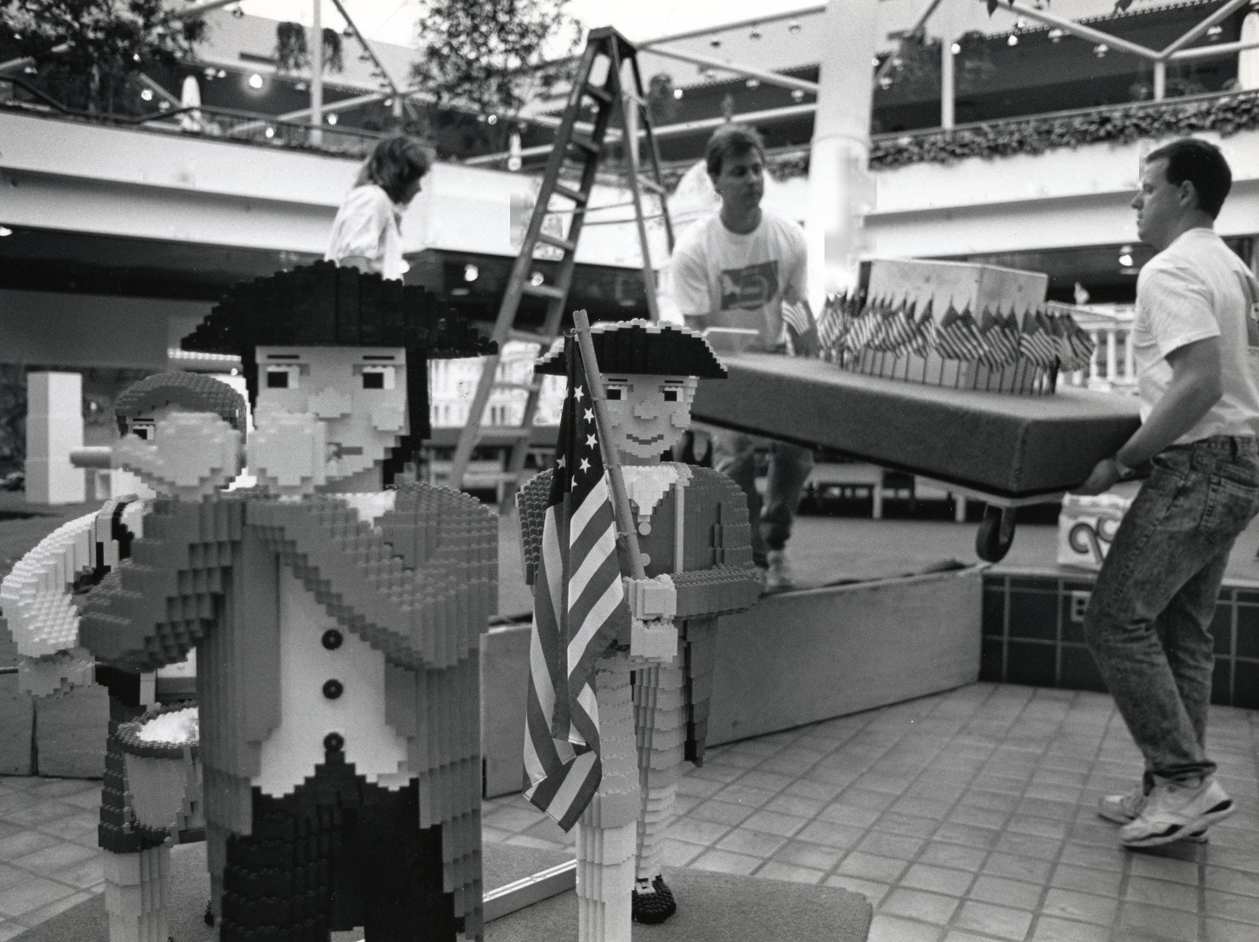 Tim Arnold, center, and Frank Jackson, right, carry part of the Lego exhibit onto the center stage at East Towne Mall. August, 1990.