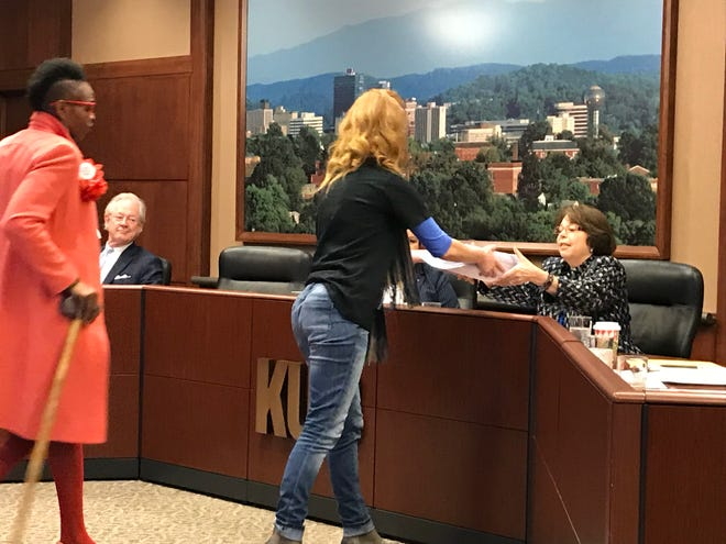 Laura Humphrey of Renew, Tennessee, followed by Tiara-Lady Wilson, presents a petition to Knoxville Utilities Board member Kathy Hamilton on Jan. 17, 2019. Renew TN, an offshoot of the Southern Alliance for Clean Energy, seeks to halt increases in KUB's basic electric service charge.