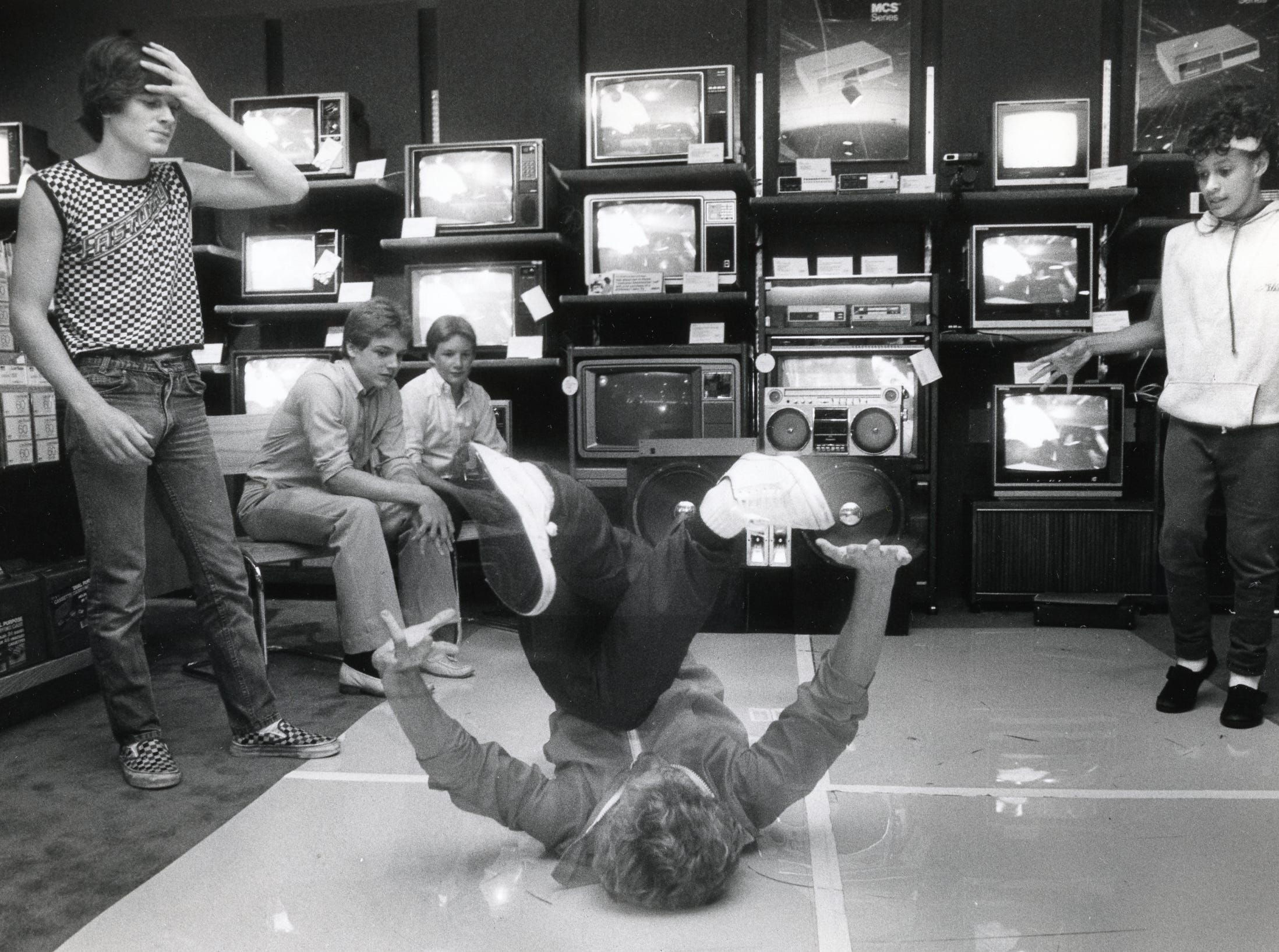 A break dancer performs for a crowd of friends at East Towne Mall, July, 1984.