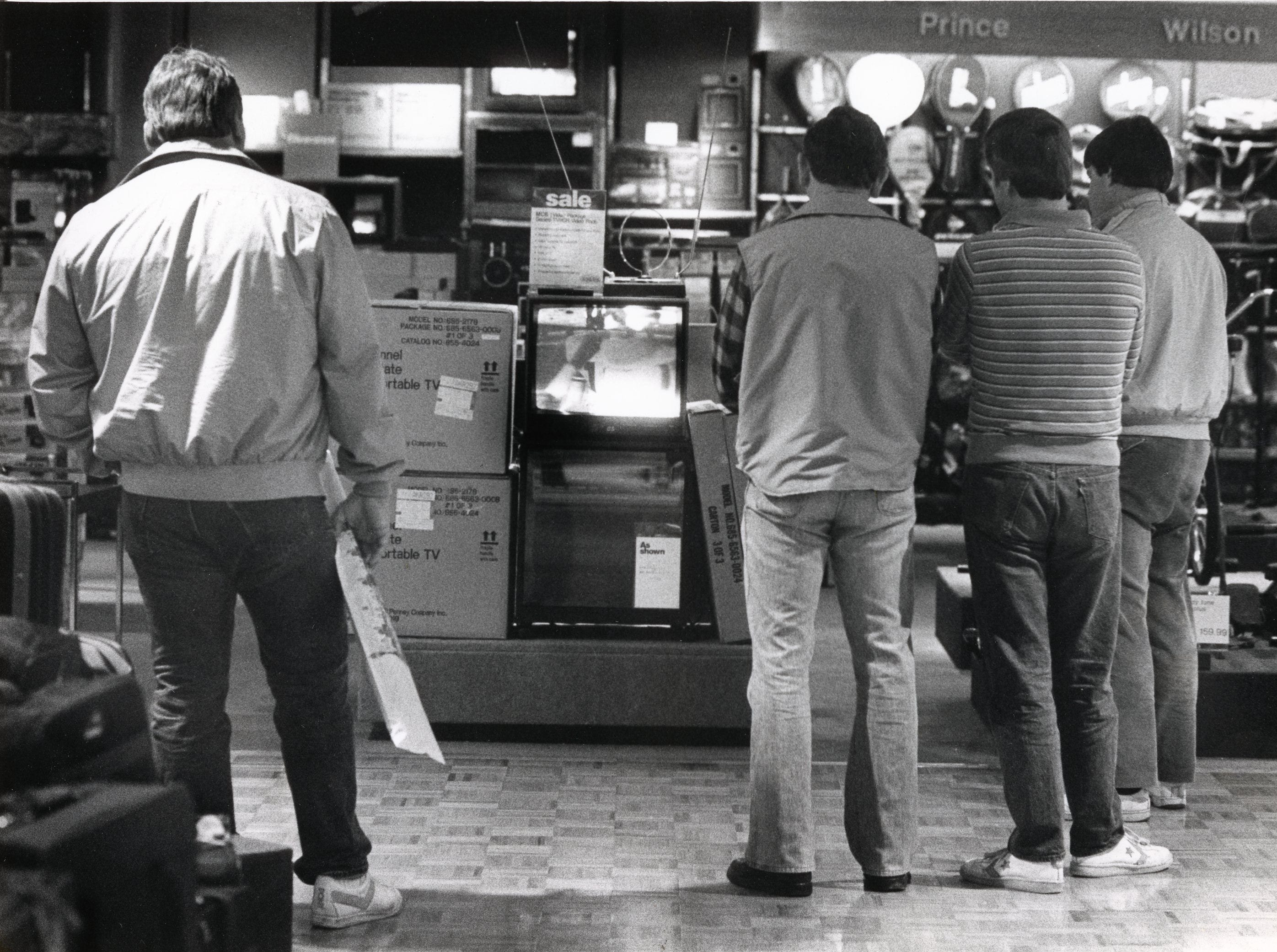 Football fans gather in front of a television display at J.C. Penney on New Years Day while wives shop.