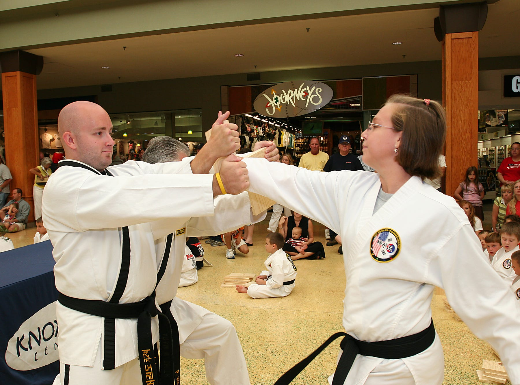 Jenny Spangler, 12, of Horace Maynard Middle School, breaks through a board while Adam Smith of Fountain City braces it during TaeKwonDo International's 7th Annual Board Break-a-thon at Knoxville Center mall on Labor Day.