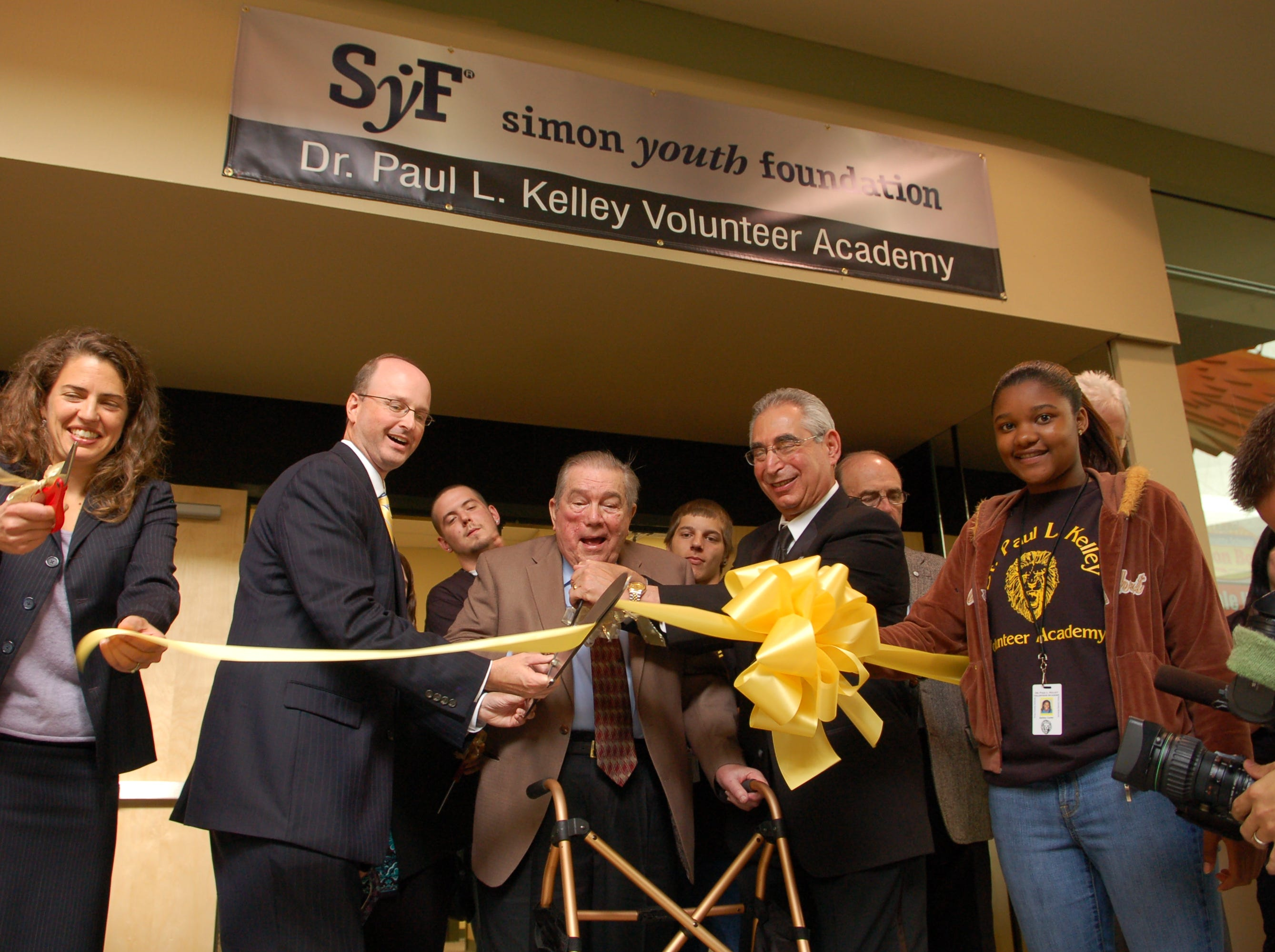 Dr. Paul L. Kelley, center, on Nov. 1, 2010, helps cut the ribbon for the official opening of the Dr. Paul L. Kelley Volunteer Academy - Education Resource Center in Knoxville Center Mall. Front row, from left: Indya Kincannon, chairwoman of the Knox County Board of Education, Superintendent James P. McIntyre Jr., Kelley, Dr. Rick Markoff, executive vice president of the Simon Youth Foundation, and academy student Ashley Carter.