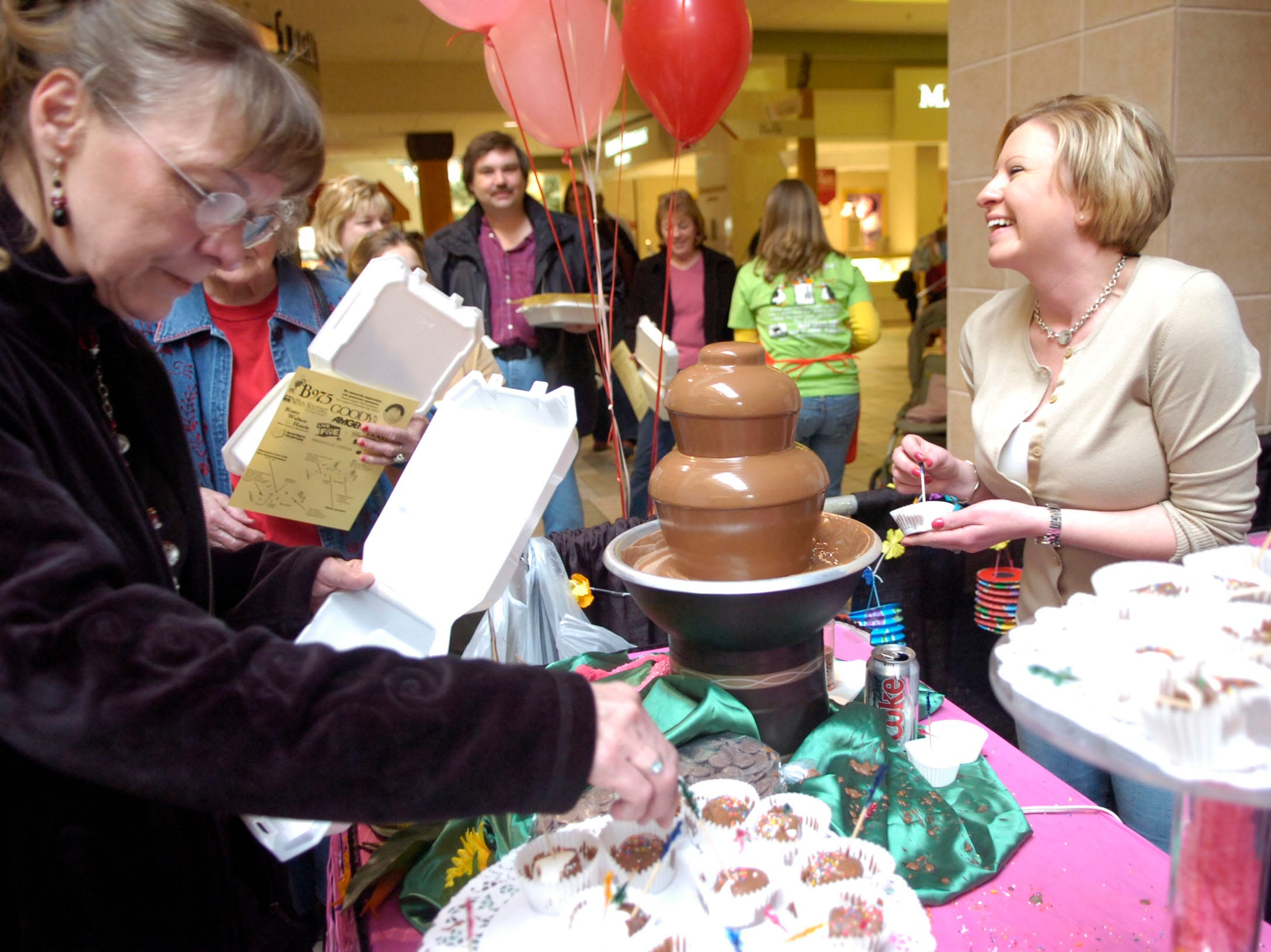 """""""Sugarbakers"""" owner Stephanie Briggs (right) passes out chocolate covered marshmallows to the crowd during the 22nd annual Chocolate Fest held at Knoxville Center Mall on Saturday. The event benefits the National Kidney Foundation of East Tennessee."""