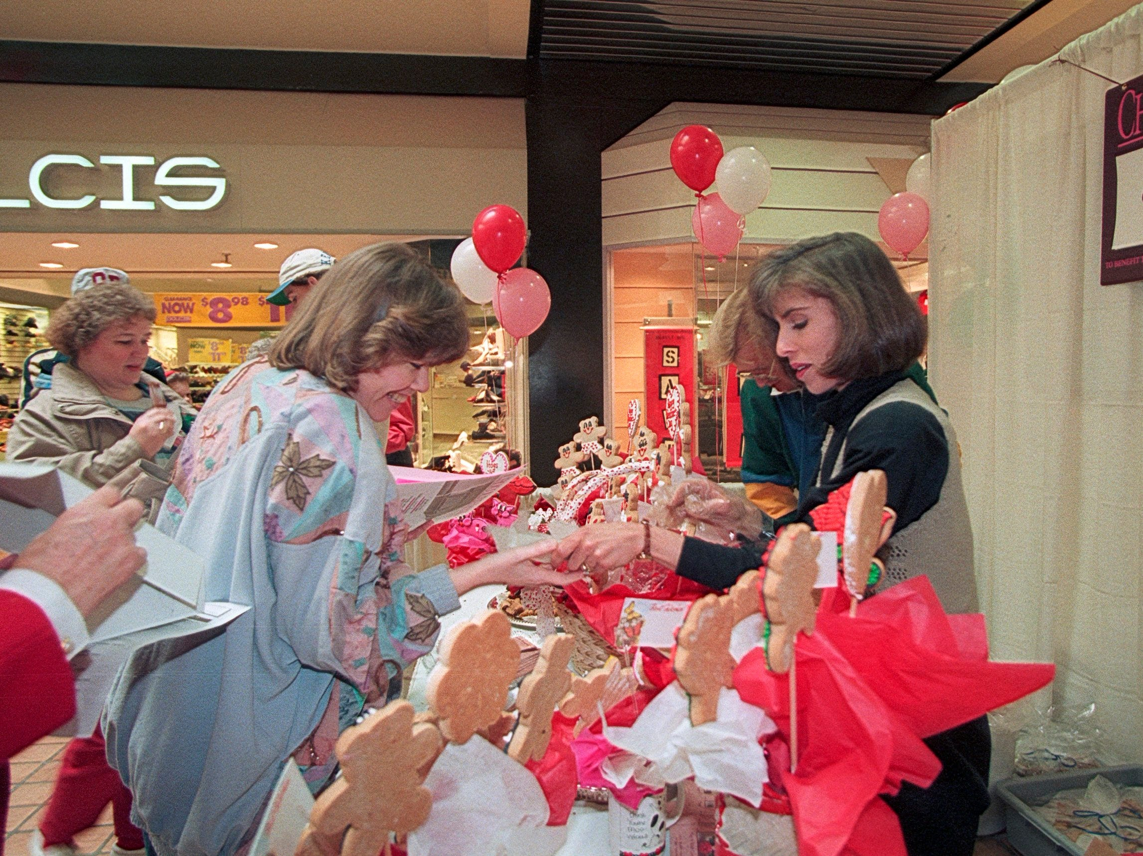 Carolyn Neimeyer, right, of the Cookie Bouquet distributes a treat to Brenda DeHart during the Chocolate Fest on Jan. 21, 1995, at East Towne Mall. (J. Miles Cary/News Sentinel)
