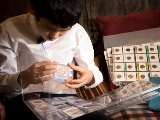 Aaron Rosen, 11, looks through his collection of early half-dollar coins on Jan. 16, 2019. He has one that dates to 1813.
