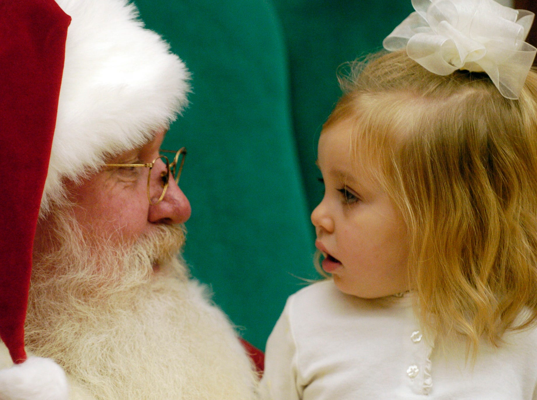 """Sunday,December 16,2007  Bryanna Ingram, 2, and Santa meet face-to-face during a visit to Santa Claus at Knoxville Center Mall. The Mall has has acquired the Haywood House, a life size replica of a turn-of-the-century home that will be the centerpiece for next year's """"Have Your Picture Taken with Santa"""" event."""