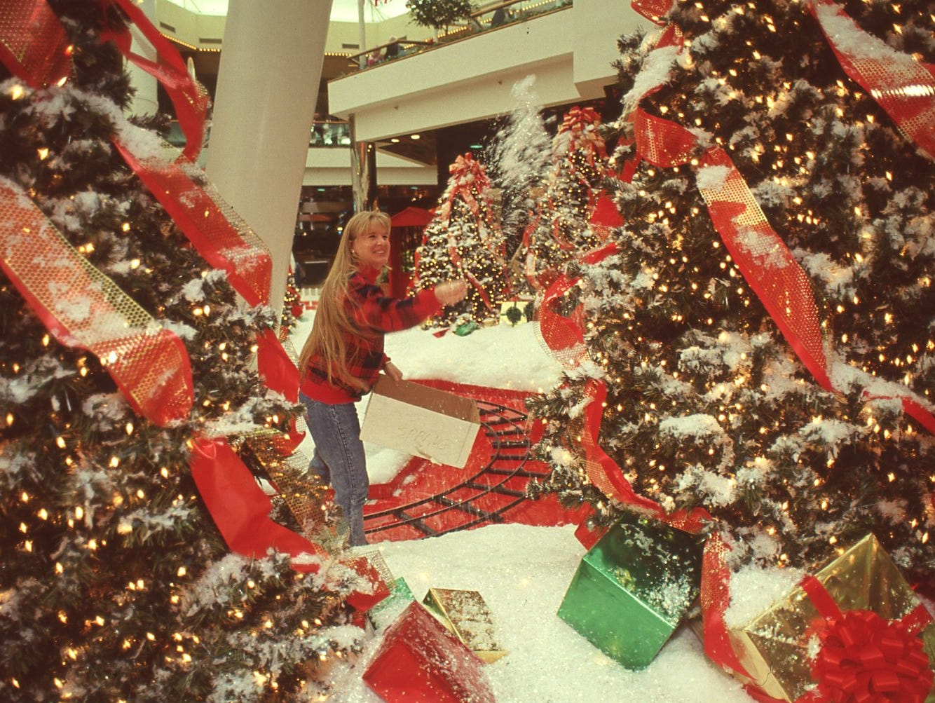 Dinah Vann, marketing assistant at East Towne Mall, throws fake snow to touch up the decorated Christmas trees in the mall, November, 1995.