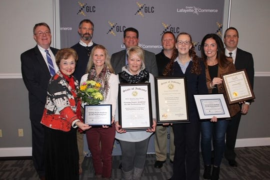 Alicia Kuckartz, front row second from the left, is presented with several awards along with the Small Business of the Year Award from the Greater Lafayette Commerce.
