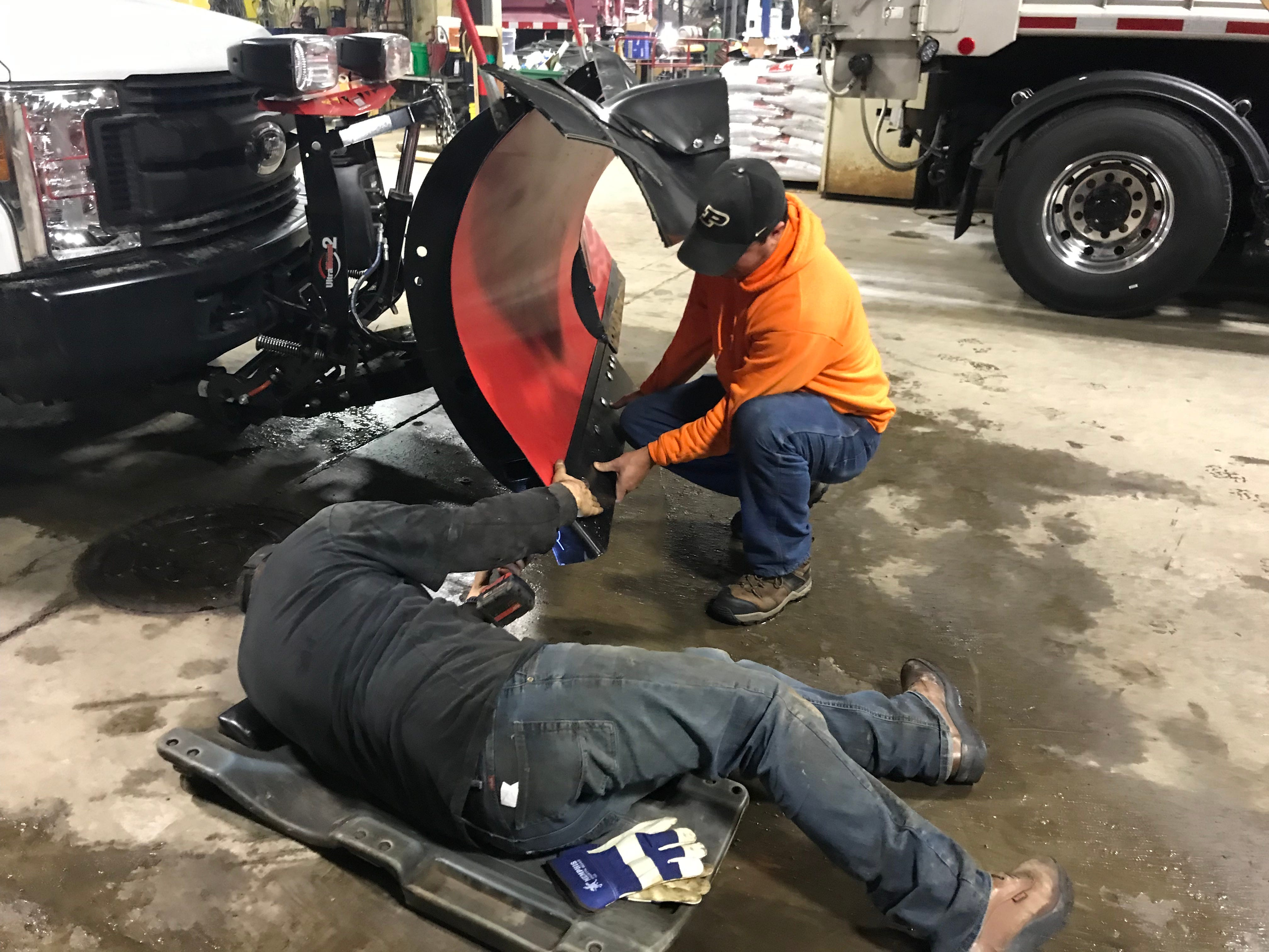 Doug Perkins and Jeremy Stinson of the West Lafayette Street Department replace a snow plow bade on a pickup truck in preparation for Saturday's snowstorm, which is expected to bring 4 to 5 inches of snow and high winds.