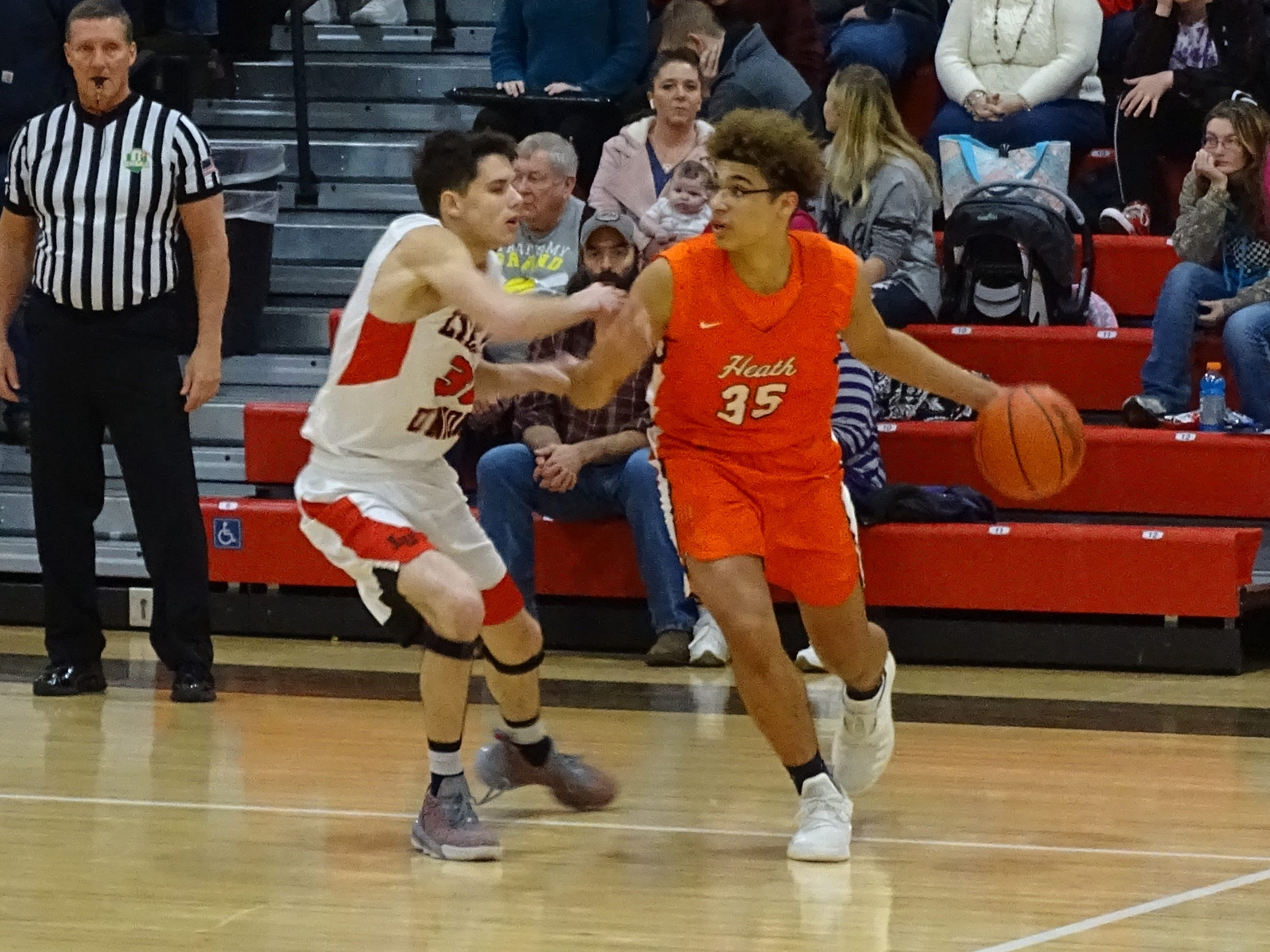 Heath's Keylan Williams dribbles past Liberty Union's Hunter Antritt during a nonconference game on Wednesday. The Lions pulled away in the second half for a 61-40 victory.
