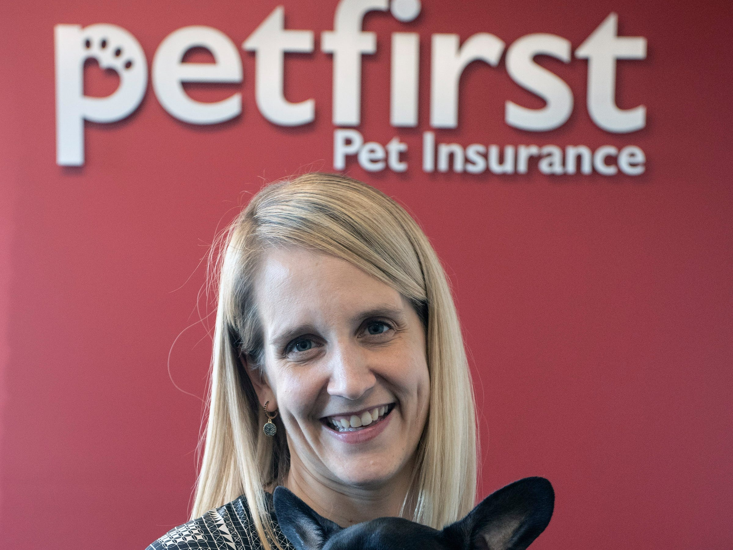 PetFirst CEO Katie Blakeley holds a sleepy French bulldog named Winston in the lobby of the pet insurance company's Jeffersonville office. Jan. 10, 2019