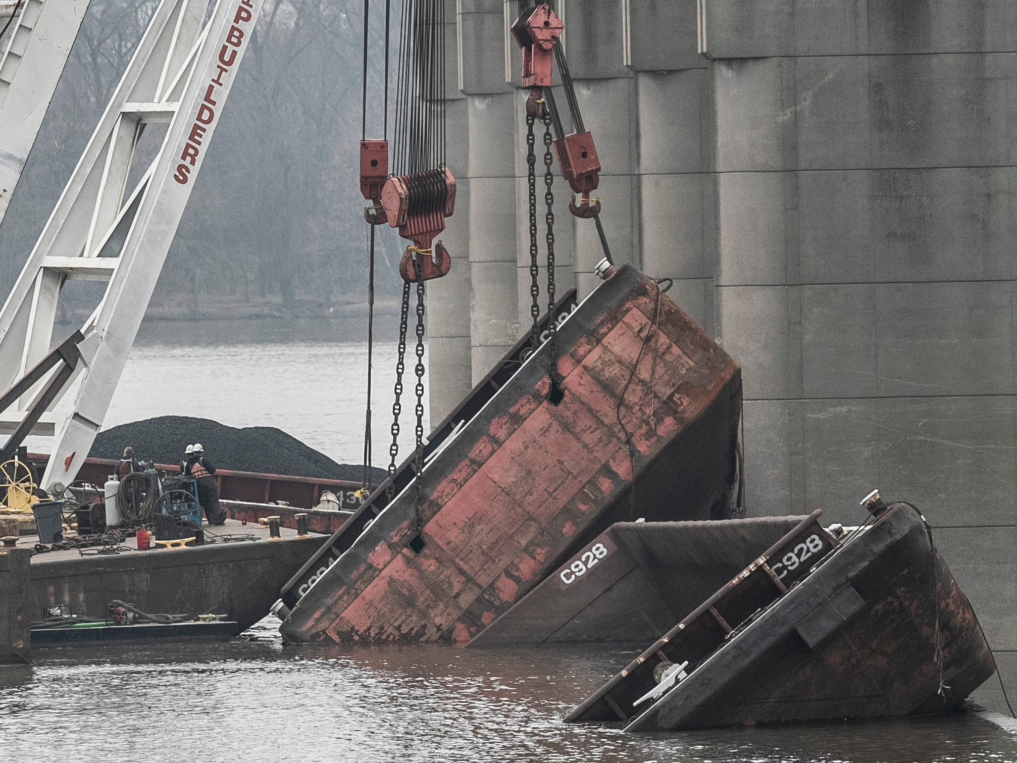 Work still continues on barge recovery near the dam at the Falls of the Ohio Wednesday, January 16, 2019. Seven barges have sunk since the night of Dec. 25, when a barge hit the Clark Memorial Bridge as it was being towed upstream. The crash caused 15 barges to break loose from the towing vessel and float downriver to the dam.