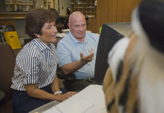 Dick Windbigler, who retired as Mansfield Senior athletic director in 2011, is seen in this file photo showing his replacement, Laurie Romano, how to enter data into the OHSAA schedule data base.