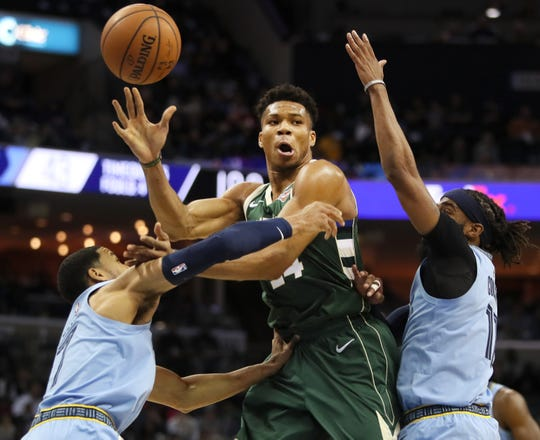 Milwaukee Bucks forward Giannis Antetokounmpo passes the ball out of a double team by Memphis Grizzlies guard Garrett Temple, left, and Mike Conley during their game at the FedExForum on Wednesday, Jan. 16, 2019.