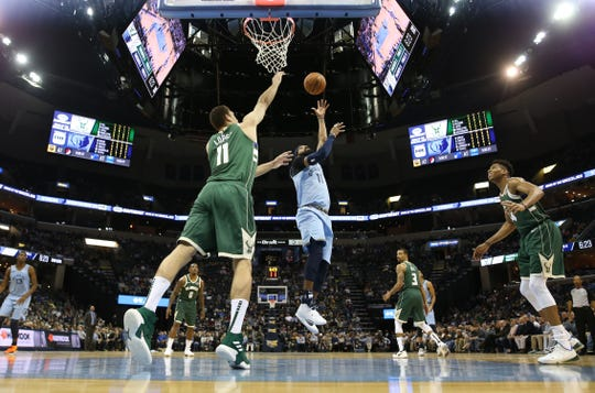 Memphis Grizzlies guard Mike Conley lays the ball up over Milwaukee Bucks Brook Lopez during their game at the FedExForum on Wednesday, Jan. 16, 2019.