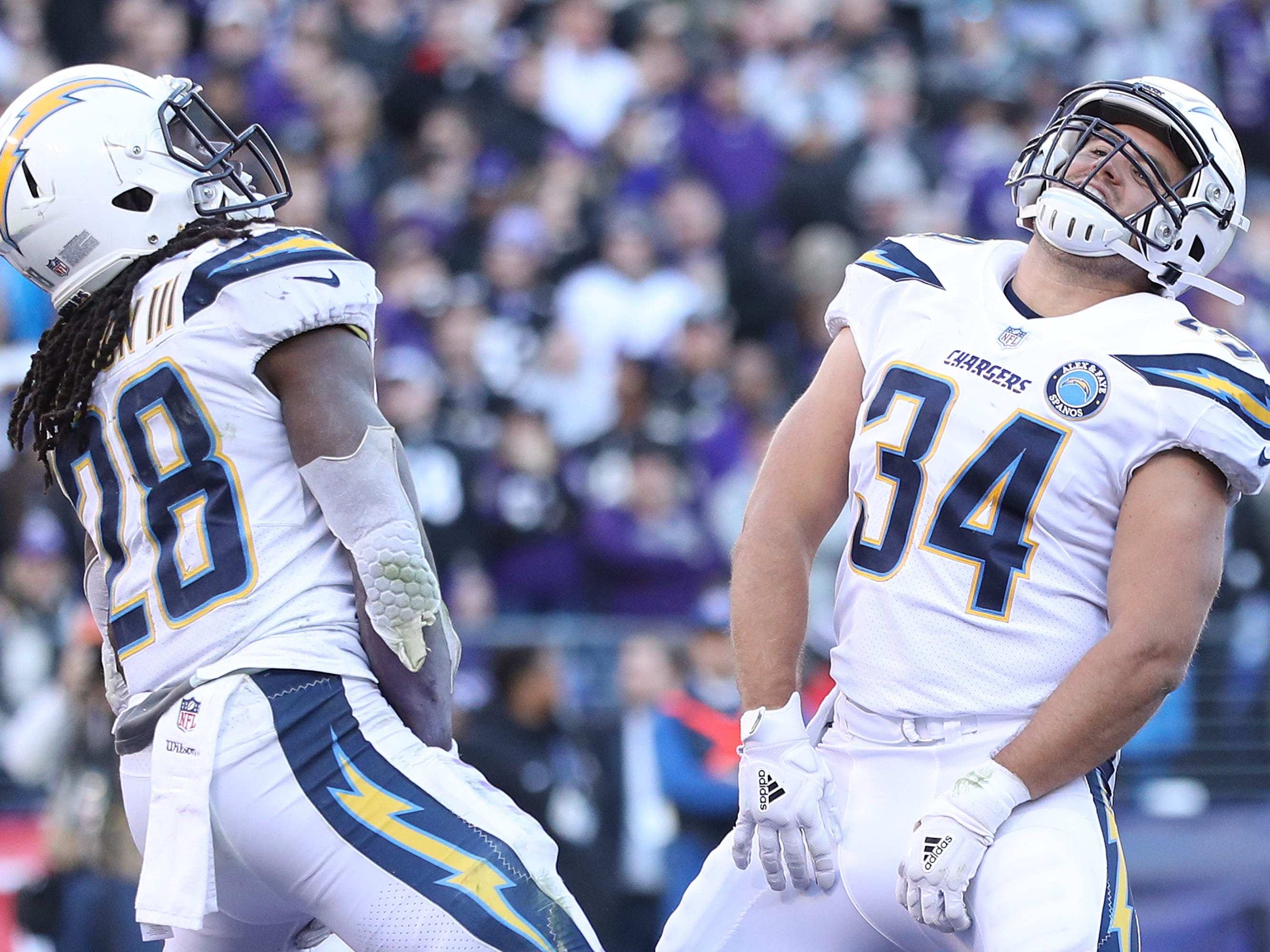 Melvin Gordon of the Los Angeles Chargers celebrates with Derek Watt (34) after scoring a one-yard touchdown against the Baltimore Ravens during the fourth quarter in the AFC Wild Card Playoff game at M&T Bank Stadium on Jan. 6, 2019 in Baltimore, Maryland. The Chargers won, 23-17.