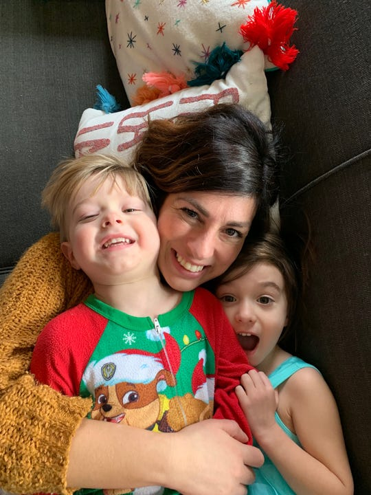 Krysta Hutton snuggles with her two young kids, Rex, 3, and Ruby, 4.