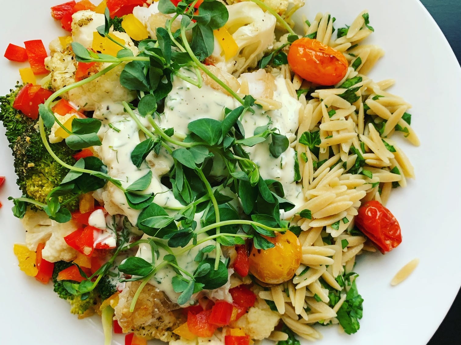 Pan-seared cod with vegetable orzo salad (from her blog) is garnished with microgreens.