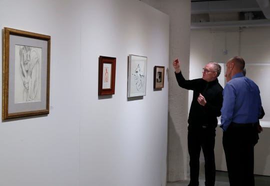 Guests view artwork in various forms of ink and paper at the opening of the new art gallery.