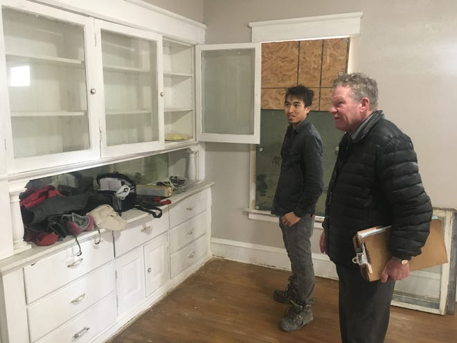 Jimmy Saenphonphakdee  (left) and Brian Pellett, a housing rehab specialist for the City of Milwaukee's Neighborhood Improvement Development Corp., talk about renovations at a tax foreclosure house Saenphonphakdee bought in the city's Cold Spring Park neighborhood.