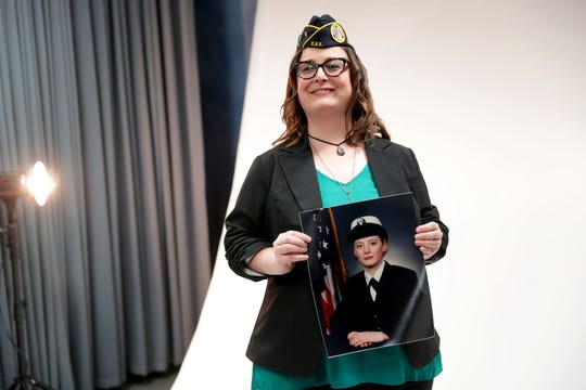Navy veteran Laura Felten poses with her service photo at the Zablocki Veterans Affairs Medical Center in Milwaukee on Thursday. Felten is a social work coordinator for a re-entry veterans program at  the VA. The photo session was part of the I Am Not Invisible project.