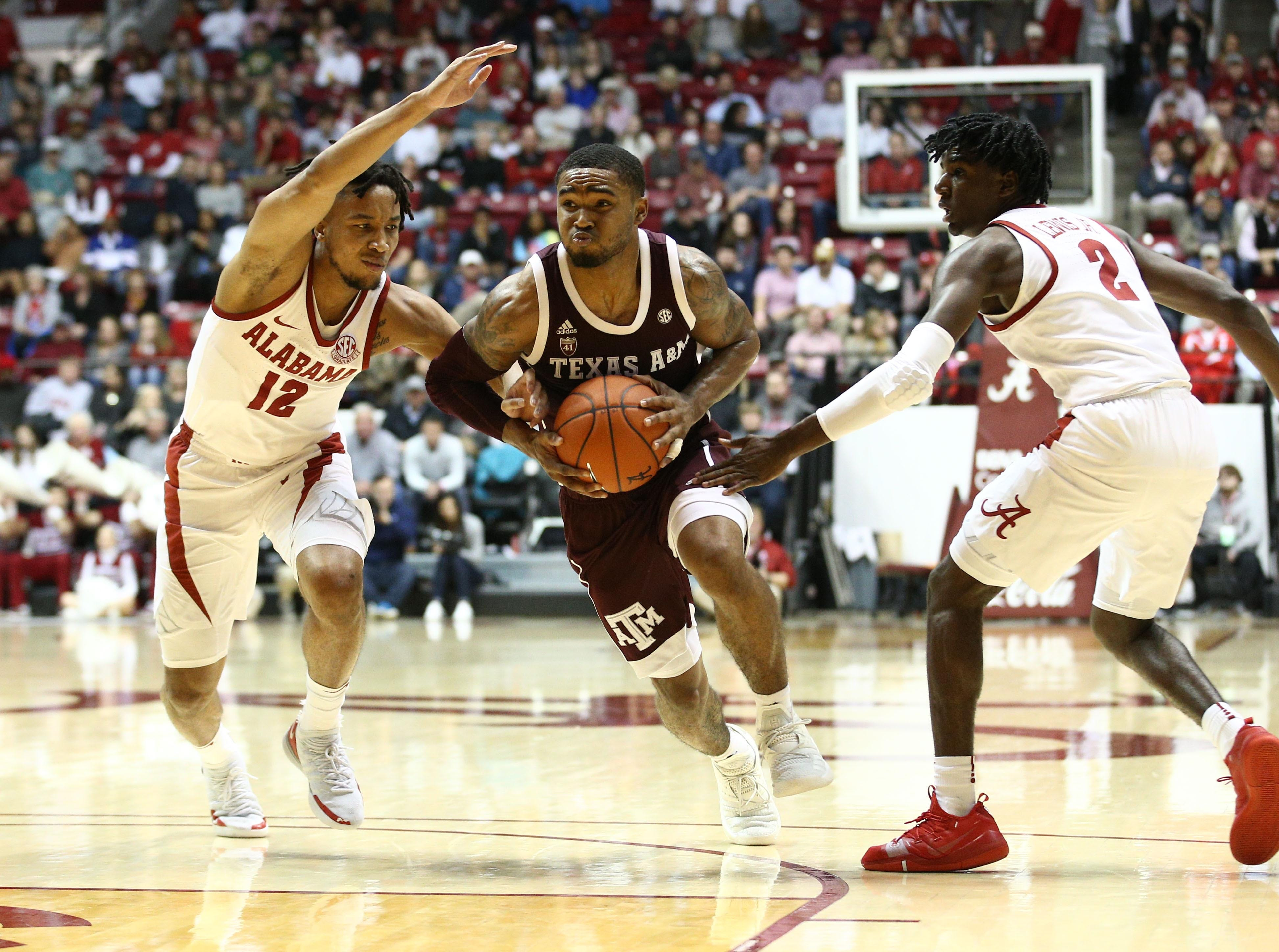 Jan 12, 2019; Tuscaloosa, AL, USA; Texas A&M Aggies guard TJ Starks (2) drives to the basket against Alabama Crimson Tide guard Dazon Ingram (12) and guard Kira Lewis Jr. (2) during the first half at Coleman Coliseum. Mandatory Credit: Marvin Gentry-USA TODAY Sports
