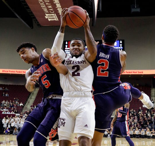 Texas A&M guard TJ Starks (2) is defended on a rebound between Auburn forward Chuma Okeke (5) and guard Bryce Brown (2) during the first half of an NCAA college basketball game, Wednesday, Jan. 16, 2019, in College Station, Texas.
