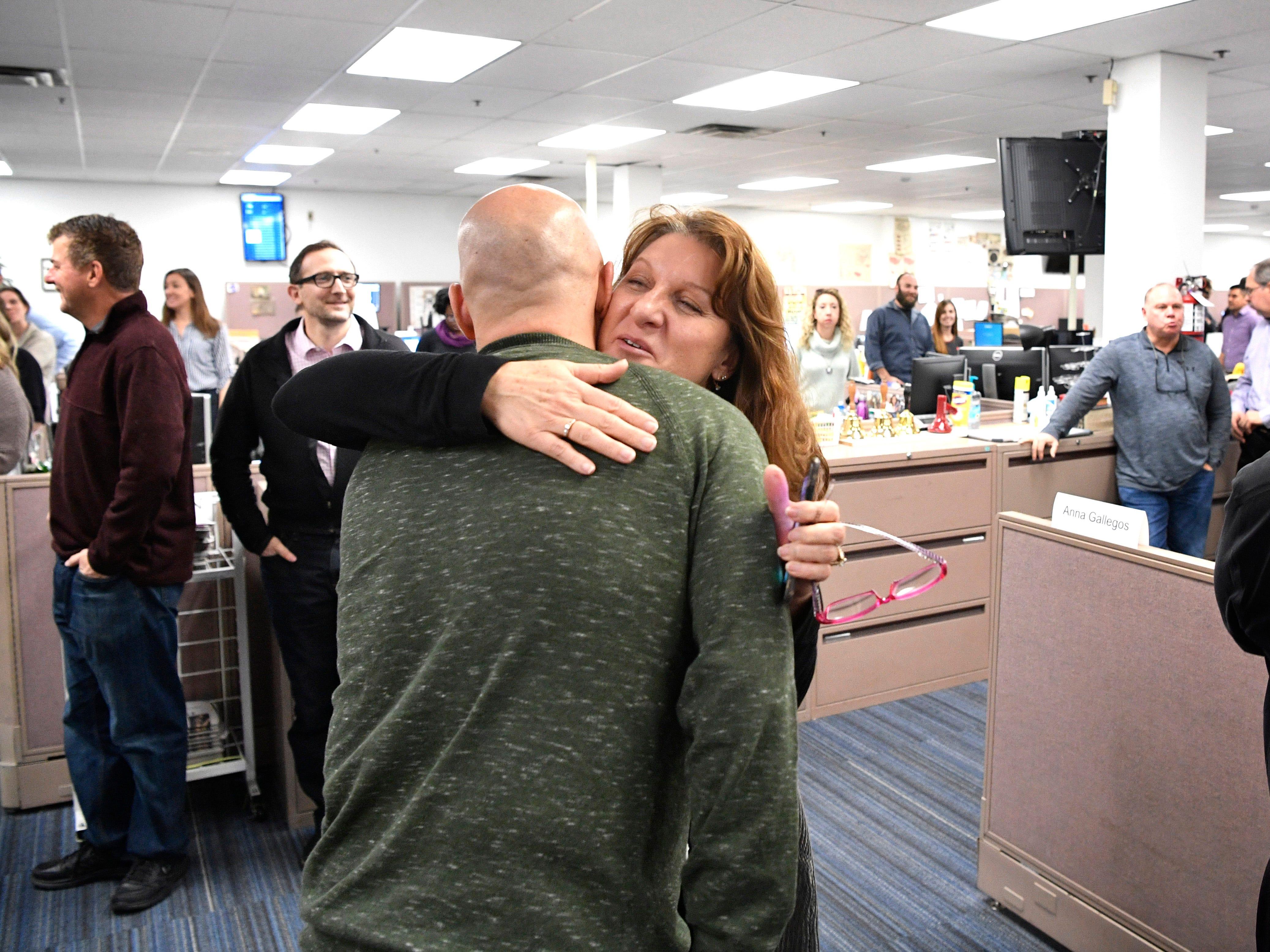 Maria De Varenne hugs Jeff Walter during his retirement party in The Tennessean newsroom Wednesday, Jan. 2, 2019.