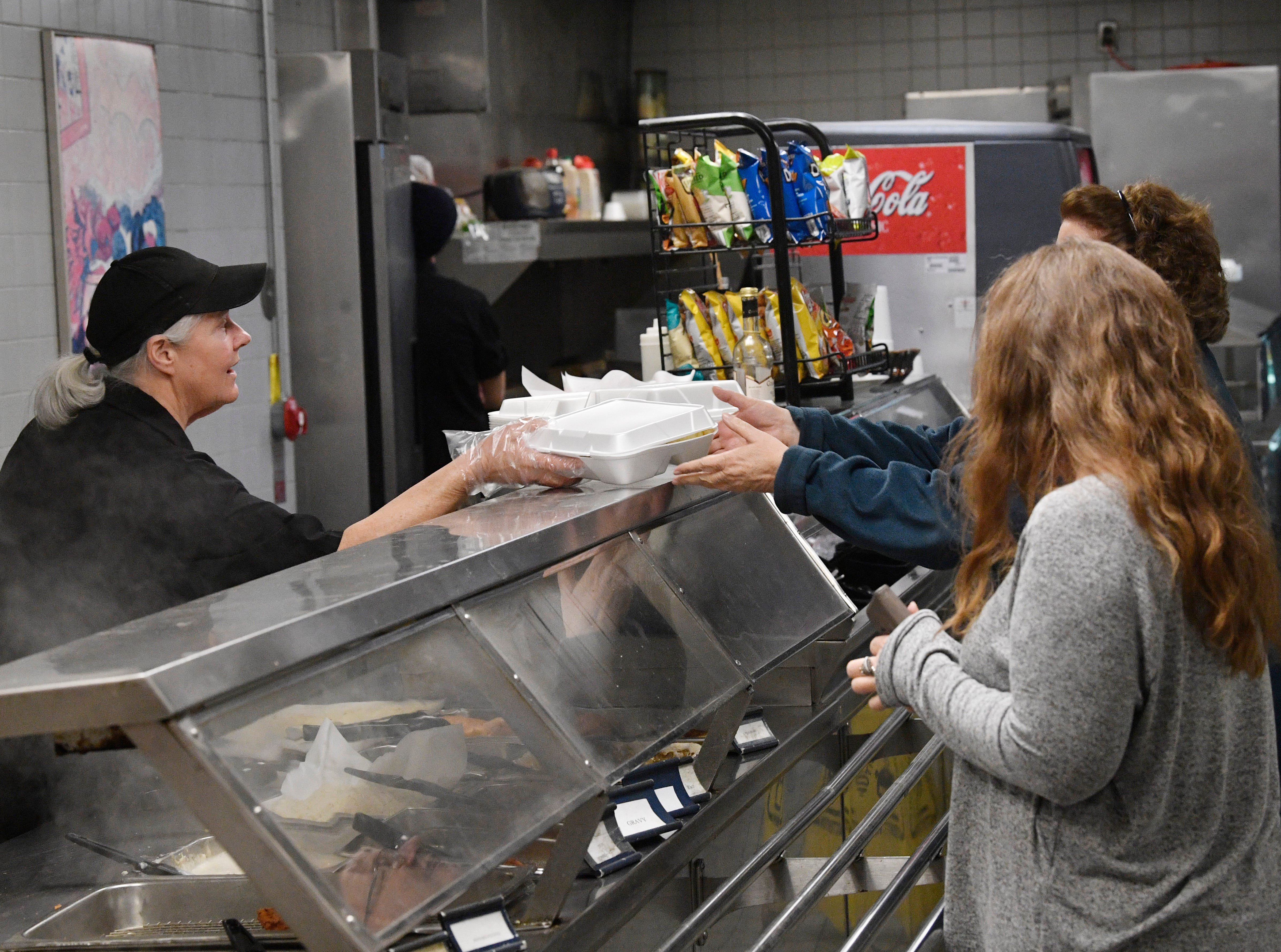 Judy Pourviseh dishes out food in the cafeteria at 1100 Broadway on Wednesday, Jan. 16, 2019, in Nashville.