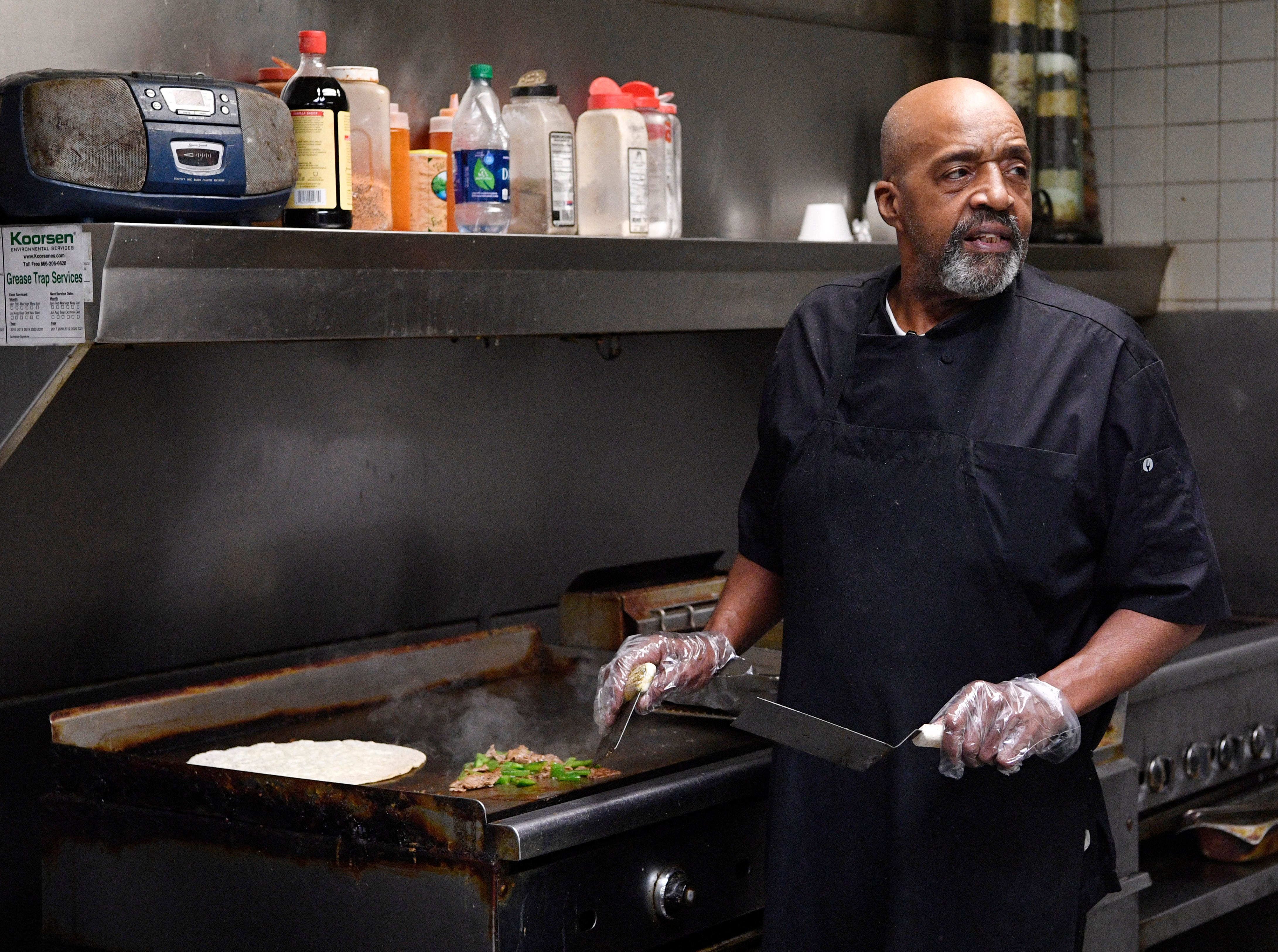 Winston Franklin works the grill in the cafeteria at 1100 Broadway on Wednesday, Jan. 16, 2019, in Nashville.