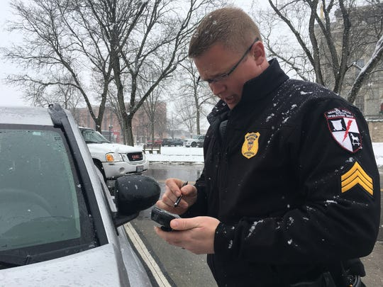 Newark police Sgt. Clint Eskins demonstrates how to electronically chalk a parked vehicle using a handheld device in downtown Newark on Thursday, Jan. 17, 2019.