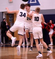 Granville's Will Skerbetz (left) and Brody Bitters (right) mob Brody Ley (center) after he sunk a buzzer beating three to send the Blue Aces in to overtime against Johnstown. The Blue Aces defeated the Johnnies 35-32 in double overtime on Wednesday, Jan. 16, 2019 at Granville High School.