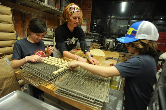 Rachel Wyman, owner of Montclair Bread Company, enlists the help of her children Josie and Keegan to make donut nuggets for federal government workers at Newark Airport.