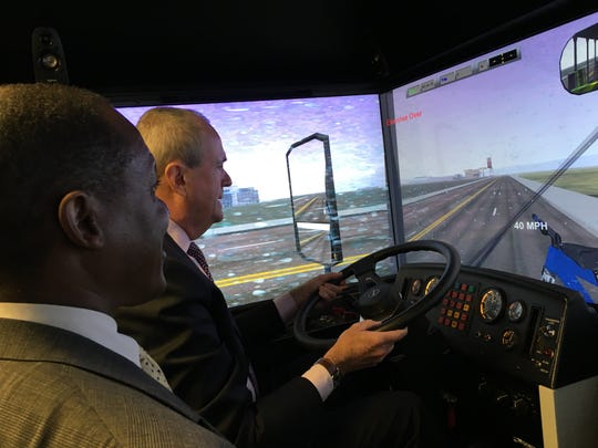 Michael Fisher, chief instructor of operation training for NJ Transit, watches Gov. Phil Murphy operate the bus simulator at the agency's training center in Newark. Fisher instructed Murphy to crash the bus to end the simulation, and the governor did.