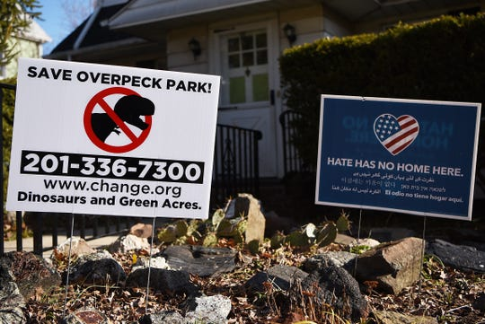 Save Overpeck Park signs with an anti-dinosaur logo are showing up in and around the Teaneck and Leonia area. People are opposed to the dinosaur theme park moving into in Overpeck Park claiming Dinosaurs and Green Acres Don't Mix. A yard sign in Teaneck on Thursday January 17, 2019.