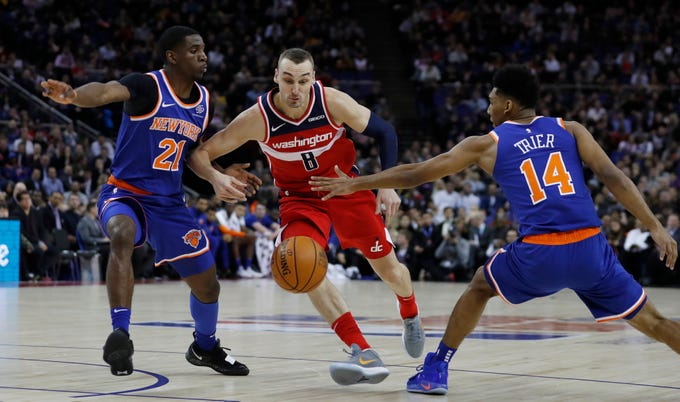 Washington Wizards forward Sam Dekker (8), right, drives to the basket as New York Knicks guard Damyean Dotson (21), left, and his teammate guard Allonzo Trier (14) defend, during an NBA basketball game between New York Knicks and Washington Wizards at the O2 Arena, in London, Thursday, Jan.17, 2019.