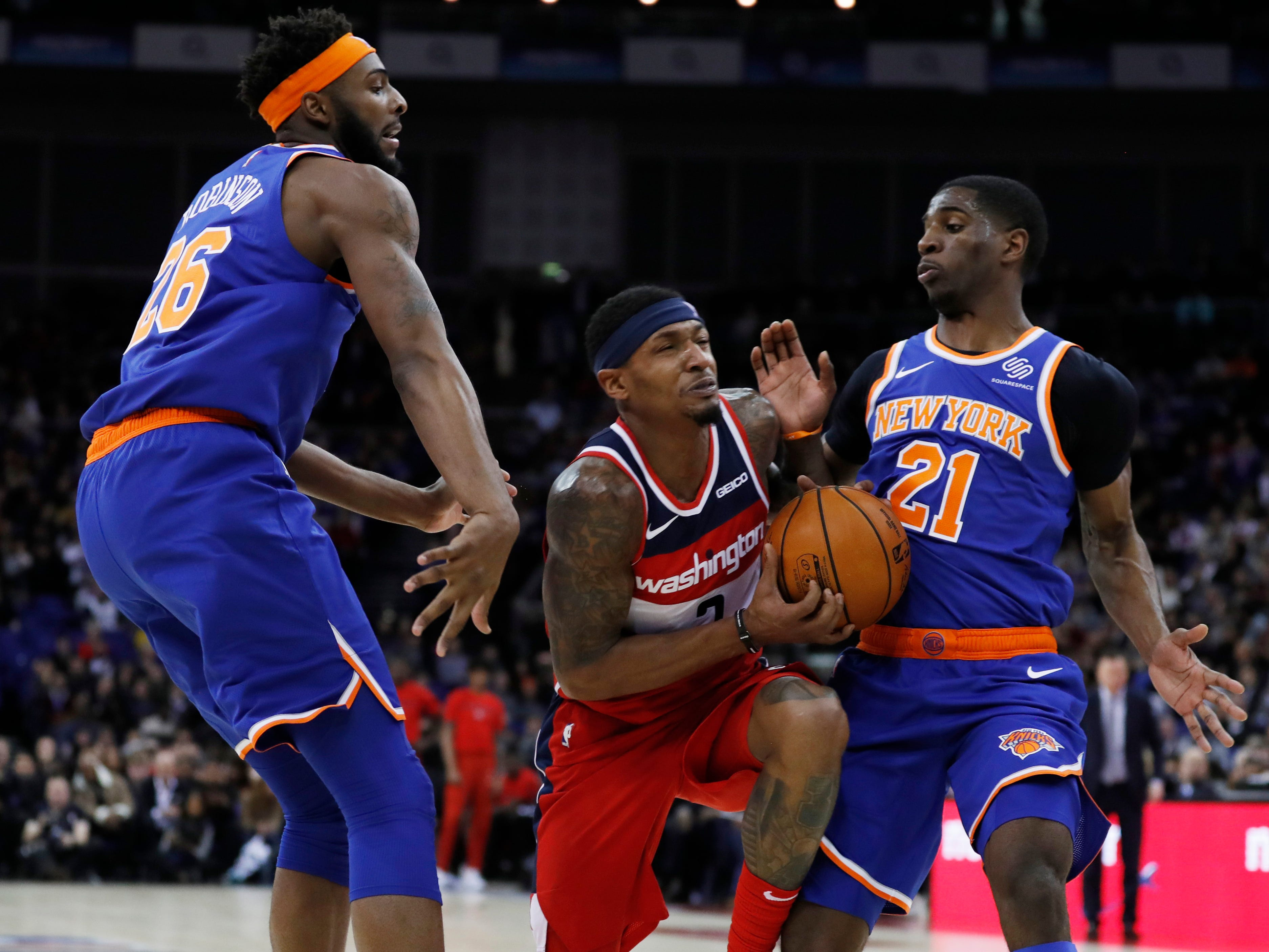 Washington Wizards guard Bradley Beal (3),center, drives to the basket flanked by New York Knicks center Mitchell Robinson (26), left, and his teammate guard Damyean Dotson (21), during an NBA basketball game between New York Knicks and Washington Wizards at the O2 Arena, in London, Thursday, Jan.17, 2019.