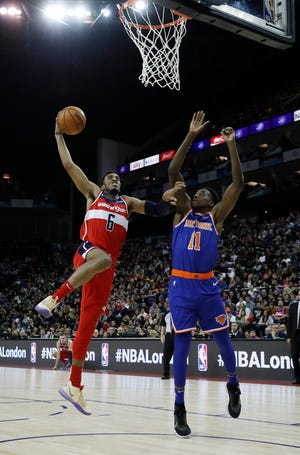 Washington Wizards forward Troy Brown Jr. (6), left, drives to the basket as New York Knicks guard Frank Ntilikina (11) defends, during an NBA basketball game between New York Knicks and Washington Wizards at the O2 Arena, in London, Thursday, Jan.17, 2019.