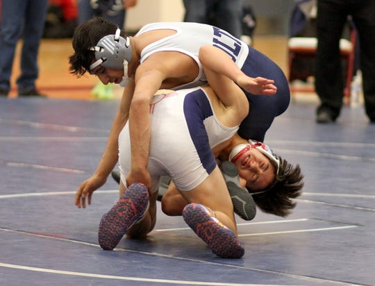 Freshman Wildcat Davy May works from the bottom to clear himself of Silver's Isaac Aguilar in Wednesday's bout at 120 pounds. May scored a 6-4 decision over Aguilar but the Fighting Colts walked away with the team victory, 63-21, at Deming High School.