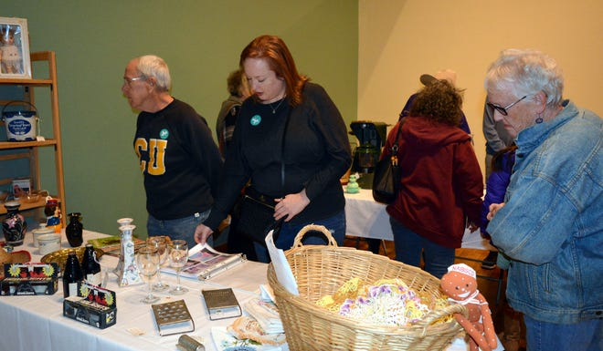 people shopping at a vendor table at last year's Antique Treasure's Show.