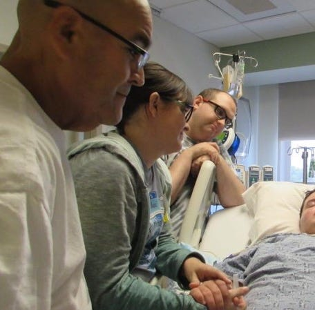 Ervie Ornelas, his wife Leah Tereasa Ornelas and stepson Ian Young look on as Ian's brother Zachary sleeps in a hospital bed during cancer treatment.