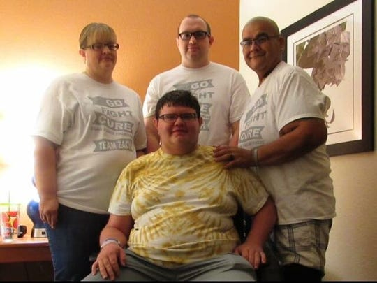 Leah Tereasa Ornelas (left), her son Ian Young, husband Ervie Ornelas and son Zachary (center) moved in together to save money during Zachary's treatment for brain cancer.