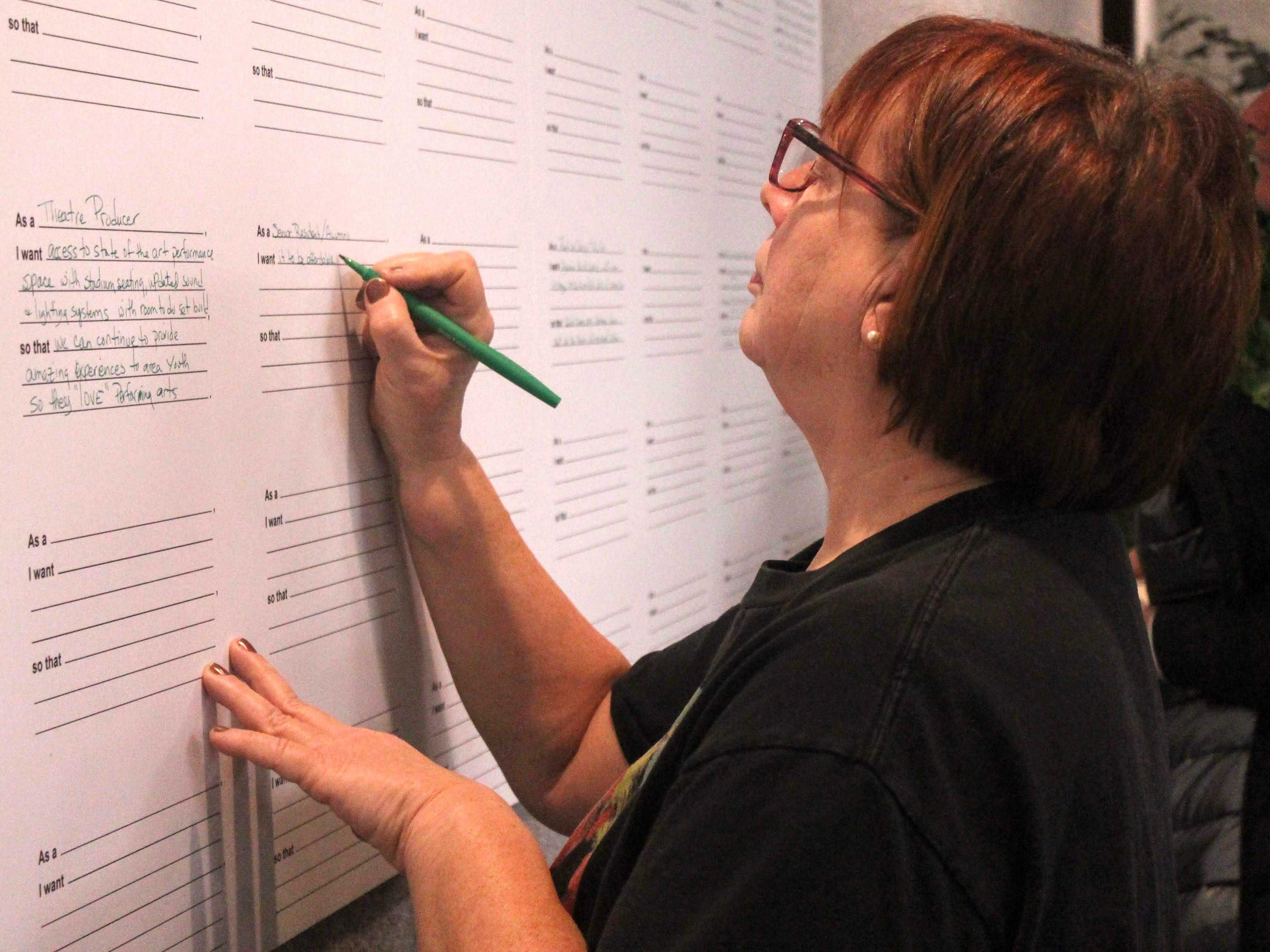 Farmington Hills resident Sandra Caldwell writes down what she would like to see at the Harrison site.